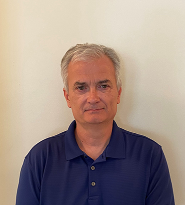 Mark Orsag, an older white man with short grey hair, smiling in a blue polo.